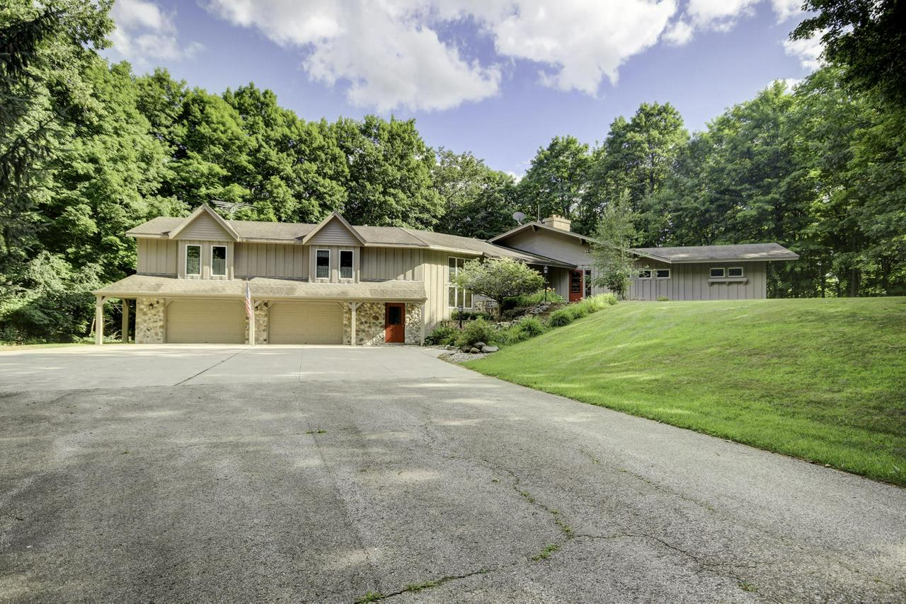 This exposed ranch is set on a 10 acre lot w/soaring old growth woods & located in the Big Cedar Lake area, providing the ultimate in natural beauty in your private nature sanctuary. The great room offers cathedral ceilings, natural fireplace, sky lights & patio doors leading to a massive multi-tiered screened deck & patio, perfect for Entertaining & nature enjoyment! The spacious kitchen offers a center island & includes all appliances. Main floor master suite w/gas fireplace has large master bathroom w/spa bath. Beautiful 4 season sunroom w/large windows! Large office/den,main floor laundry room, central vac. Separate 60'x36' wood heated shop/garage with a 60'x14' upper w/many potential uses for the hobbyist, car enthusiast, etc. Comfortable & welcoming yet truly impressive inside & out!