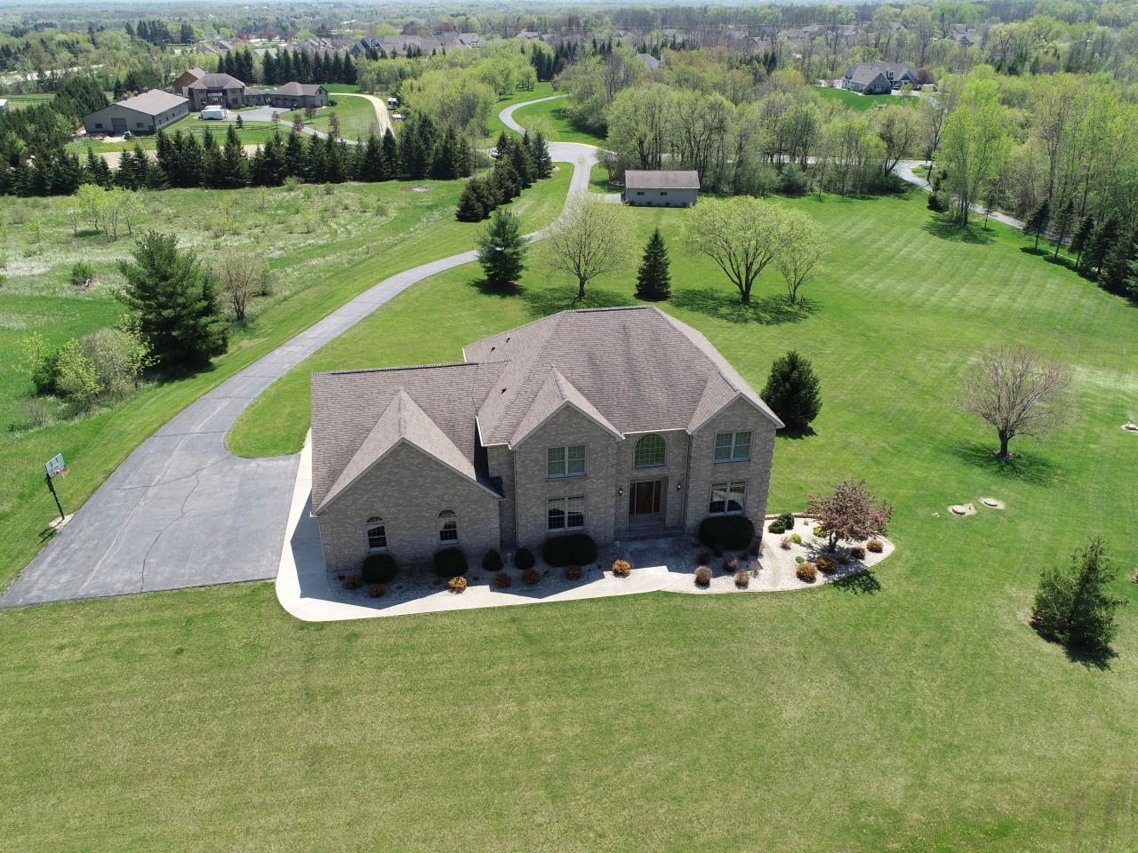 One of the highest points in Ozaukee County!! This meticulously maintained 5 BR home on 5 acres in peaceful Miller's Hill offers stunning views of the countryside & Milwaukee skyline. Sleek, spacious interior with abundant windows & soaring ceilings. White cabinetry and black granite countertops highlight the dynamite kitchen. The master suite is complete with a walk-in closet, luxurious bath & serene sitting area with city views. Relax in the finished lower level, or outside on the large deck & patio. Storage abounds in both the heated 3-plus car garage & the large heated detached garage.