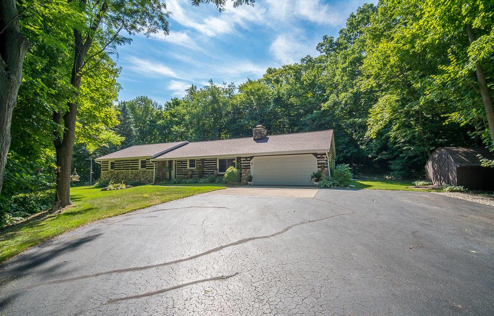 NESTLED IN OVER TWO ACRES OF WOODS AWAITS YOUR RUSTIC RANCH RETREAT WHICH FEATURES A NATURAL FIREPLACE TO COZY UP TO, 3 SPACIOUS BEDROOMS, AND A SUN ROOM FOR TAKING IN THE VIEW. ENJOY THE PRIVATE WALKING PATH THRU THE WOODS. FIND YOURSELF RELAXING IN YOUR NEW OASIS TODAY!