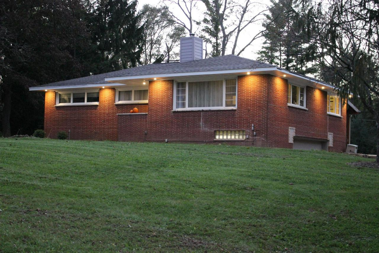 Beautiful 3 bedroom brick ranch an almost an acre! Priced for quick sale with private tree-lined yard.   Extra large living room with cozy stone natural fireplace.  Eat-in kitchen features plenty of storage and overlooks  the huge covered patio with natural gas hookup for space heating and/or grilling.   Built-in under home garage is oversized and heated.  Home is wired/piped for natural gas backup generator.  This one will not last!