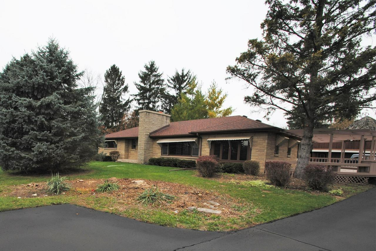 Sparkling clean brick ranch on over 1 acre of wooded land with 2 outbuildings and lots of parking. Zoned commercial so its perfect for a business or a contractor to work and live on site. Interior of home is very clean and freshly painted.  Large living room with French doors and fireplace. Family room has wet bar.  Hardwood floors in most rooms. First floor office or perfect spot for main floor utility room. Huge kitchen/dinette.  2 large outbuildings are 1512' and 864' plus carport off of larger building.