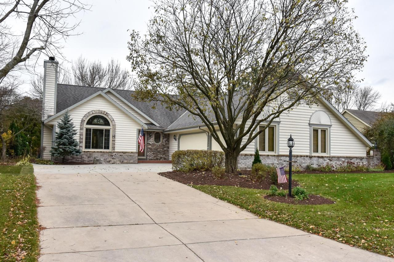 Well maintained ranch located in the heart of Menomonee Falls! Great room with cathedral ceilings and brick natural fireplace. Kitchen offers hardwood floors, pantry, planning desk and breakfast bar opening to dinette with patio doors to deck and patio. Spacious private yard with mature trees. Master bedroom suite with walk in closet, double sinks, tile floor, shower stall and whirlpool tub. Partially finished lower level with wet bar, media room, den, 3rd full bath and storage area.  First floor laundry. Neutral decor, 6 panel doors throughout. Newer windows with a transferable warranty. HSA home warranty included.