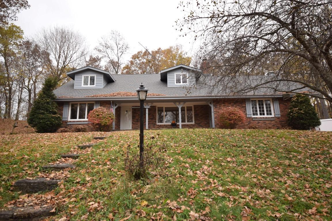 Come see this private 3 BR, 2.5 BA home on 7.86 acres that abuts the Erin Hills golf course.  Features include large living room with brick fireplace, formal dining room, eat in kitchen, 1st floor laundry, main floor bedroom and full bath.  Huge lower level recroom.  Private backyard with tons of mature trees and walking paths and lot goes all the way back to the golf course.  Located near Erin school as well.  New roof and exterior recently painted. Tons of potential.  Call today!