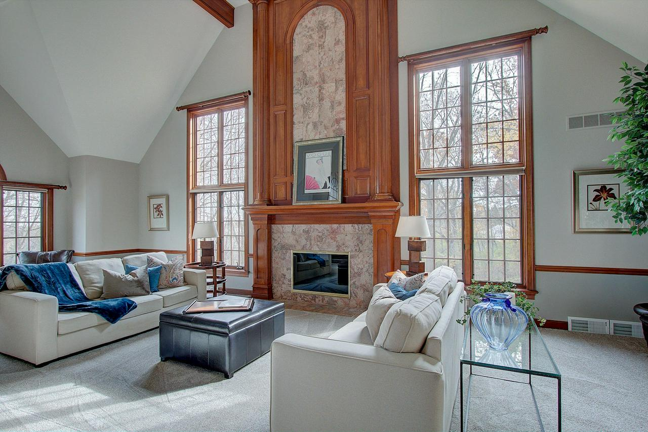 Welcome home to this 5700 sq. ft. home made for entertaining. Set high on a hill with a sweeping view and back patio surrounded by mature trees. Inside the grand Great Room and fireplace lead to a bonus Sun Room complete with wet bar, walls of windows, and skylights. The Kitchen has plenty of storage surrounding the center island and separate Dinette area with patio doors to the outside. Beautiful inlaid wood floor sets the tone in the formal Dining Room. An office, guest bedroom, and full bath complete the first floor. Upstairs is the gracious Master Bedroom suite, three additional large bedrooms, and a full bath. The lower level features 850+ sq. ft. Family Room complete with wet bar and fifth bedroom or office. Don't miss out--call today!