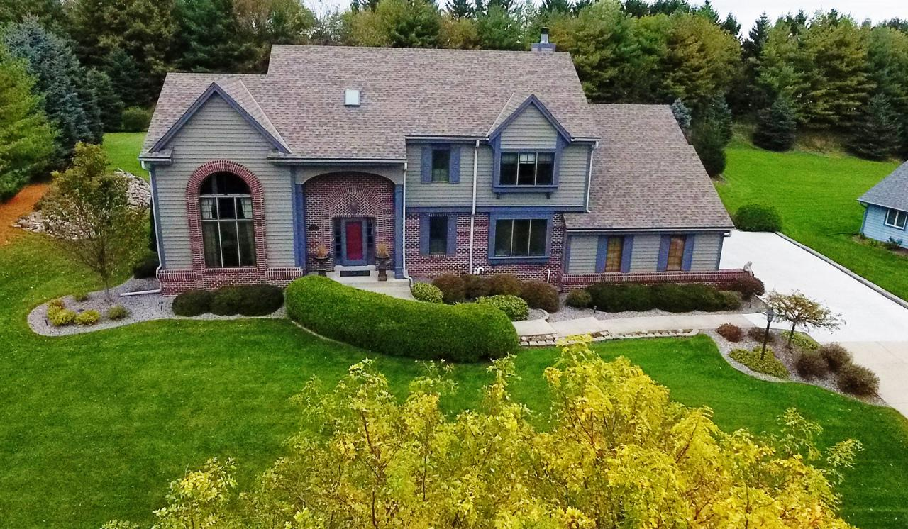 Gorgeous Trustway built home on private mature treed lot in most convenient location. Minutes to HWY 16, outstanding recreational opportunities nearby & short walk to downtown Hartland. LR, DR & foyer freshly painted w/current hues & new carpeting 2018. KIT opens to GR overlooking stunning setting & composite deck. GR: beautiful built-in cabinetry, gas FP & built-in bar, handy for entertaining. KIT birch cabinets, large island & spacious dining area. Mudroom/laundry room & half BA complete this level. LL: entertainment/gaming space, kitchenette, full BA & 4th BR w/Murphy bed. Many improvements: garage addition '10, Great room remodel 2012, new roof , skylights & windows 2015, carpeting in bedrooms 2017, on main 2018! 4 car garage will fit all of your toys. Award winning Arrowhead Schools.