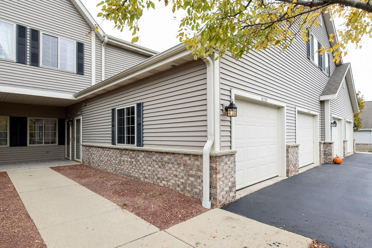 Desirable first floor condo in coveted Pine Ridge! Sought after open concept -kitchen/dining/living - with gas fireplace and private patio as the focal point. Large master bedroom with walk-in closet and private bath. Spacious 2nd bedroom also with walk-in closet. In unit washer/dryer, attached garage, & guest parking. Includes new carpet, fresh bright paint, & cleaned from top to bottom. Enjoy use of the fully equipped clubhouse, fitness center, hot tub room, and outdoor pool. Perfect location... walk to Sendiks, shops, and the Interurban bike/walk path.
