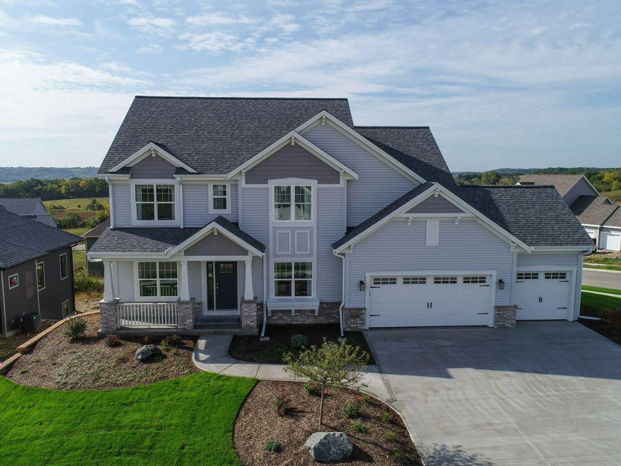 This professionally decorated builder model has one of the best views in Waukesha! This home also features southern exposure, finished basement with walkout and an Azek deck. Designed for functionality & entertaining. The deluxe Kitchen includes GE stainless steel appliances, an oversized island with Viatera quartz countertops & tile backsplash, Maple cabinets, under cabinet LED lighting.  Other finishes include Gas FP w/ tile surround w/ returns & taller mantel, deluxe Master Bathroom with walk-in tiled shower w/corner seat, swing door & rainshower head, his & hers vanities w/granite countertops. This home is move-in ready with custom painting, windows treatments, irrigation & security system and much more!