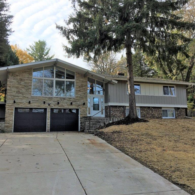 Modern, Contemporary home updated for today's life style! Open concept living space with grand vaulted ceilings and tons of light.  Elegant touches in well appointed kitchen with granite counter tops, pantry and main floor laundry area. Sun room with skylight for relaxing indoors while surrounded by sun and views of the outdoors. Tile surround shower in main bath with quartz counter tops. Huge master BR boasts luxury bath with quartz double vanity, separate shower and tub as well as skylight to bring in the beauty of natural lighting. Lower level offers stone surround natural fireplace, additional living space and full bath along  with additional bedroom with full egress. Garage is extra deep for convenient storage. This home has been extensively renovated and is sure to impress!