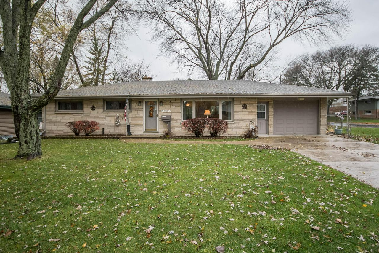 Check out this comfortable & well laid-out 3 bedroom, 1.5 bath ranch with partially finished lower level. Enjoy the convenience of being within walking distance to Village Park, schools & downtown shops. Once inside, you are welcomed into a spacious living room with sunny picture windows, a dine in kitchen with sliding patio door leading outside (easy access for BBQs!) & NEW tasteful cabinets, counters & tiled back-splash.  Rest easy with a fenced-in yard, Lannon stone exterior & newer furnace, central air, windows, concrete driveway, patio, roof & garden shed. ALL kitchen appliances, washer, dryer, snowblower & lawnmower included.