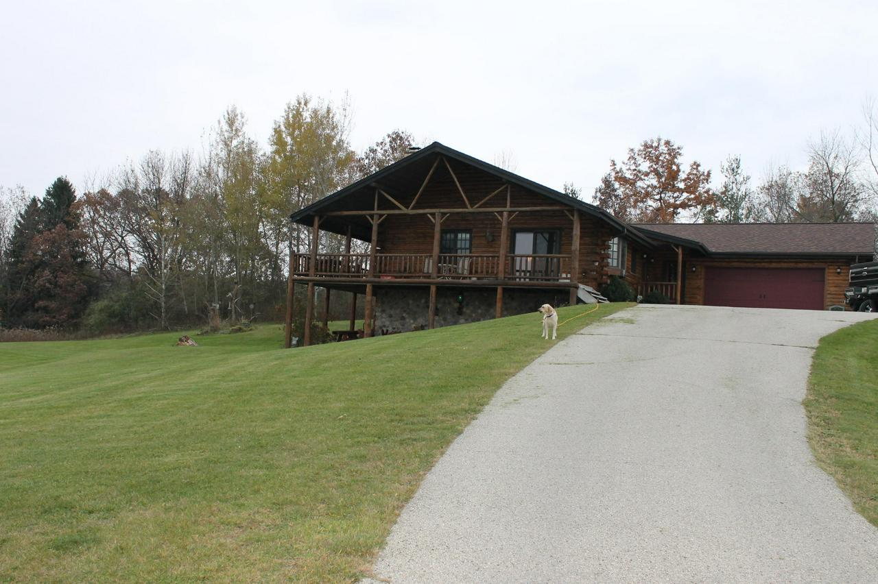 Beautiful log home situated on 13+ acres of woods with walking paths. If you are a sportsman, you have lots of room to hunt. Spectacular views of Holy Hill.  You can sit on the huge deck and enjoy watching the deer and wild turkeys and enjoy the magnificent views. Horses are allowed. Erin Hills Golf Course is close by. Natural stone fireplace and beautiful mantle in the main living area. Brand new updated kitchen, full bath and half bath in 2017. New roof was installed in 2016. Meticulously cared for. This is a move-in ready home perfect for an active family.