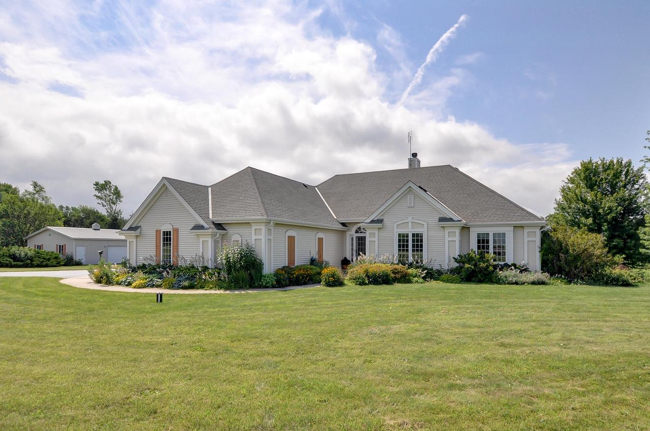 Welcome Home! This quality crafted 3 BR ranch stands out with 11' ceilings, Hickory floors, arched entries, wall of windows in  great room lets in tons of natural light! 3 season room off the kitchen, Master BR has walk-in closet,master bath with whirlpool tub & shower stall. LG mudroom off the garage & open stairway to the finished lower level w/stained concrete floors! Walkout lower level patio doors lead to a concrete patio w/a beautiful pergola & stunning array of flowers in the backyard! Frequented by deer, turkey & songbirds galore! Nestled on 5 Acres framed by Spruce & did I mention the 30x36 outbuilding with electric & concrete floor? This home has dog friendly features with doggy doors, kennel space & large wash tub! Minutes to I-43 & Village of Square! Located on a cul-de-sac.