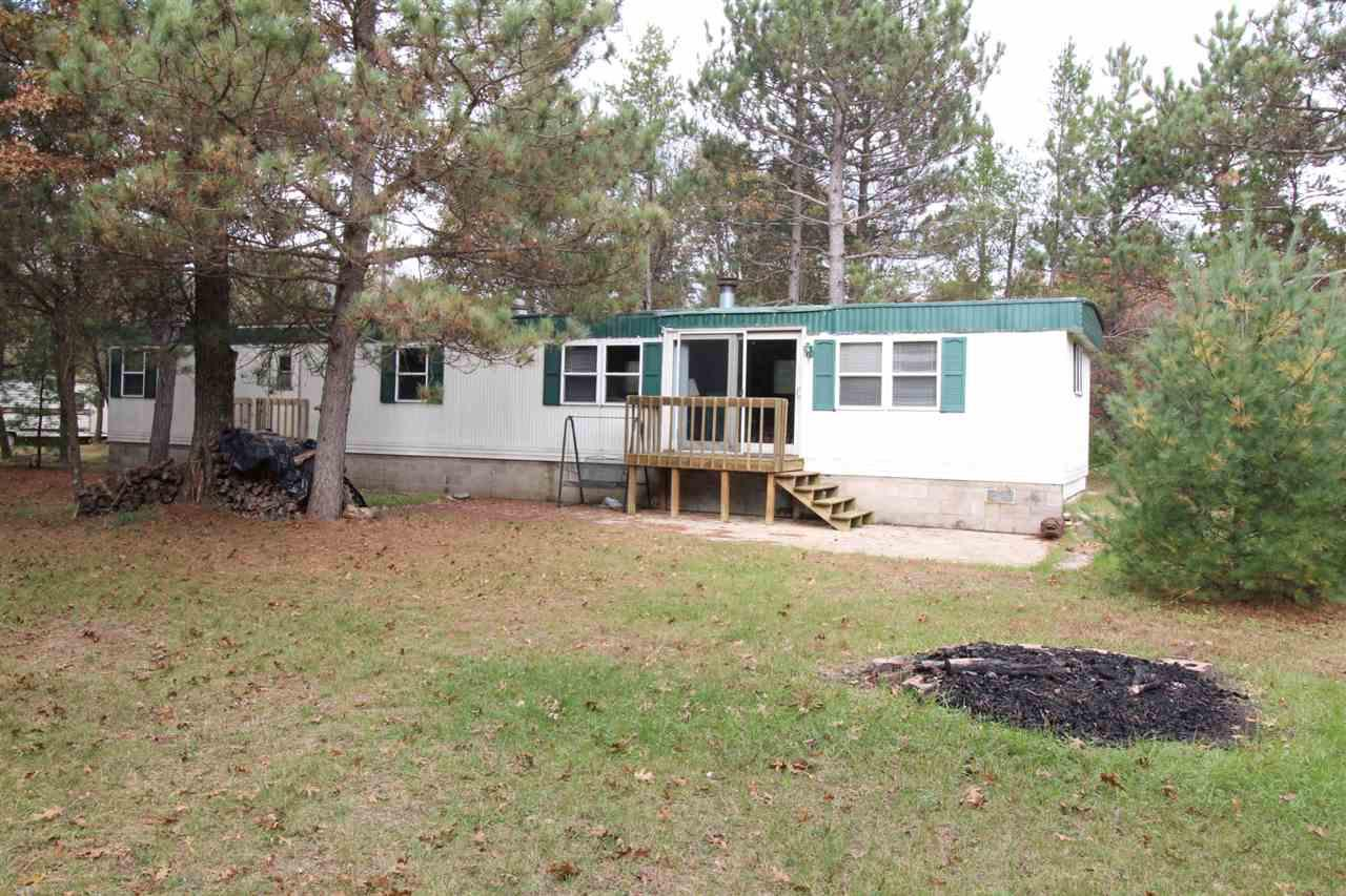Recreation fun year round - 18 acres of privacy with Dead Horse Creek going through the property, great for hunting, camping, hiking. Property located on ATV and snowmobile trails. 2 bedroom mobile, open living, dining & kitchen. 13x36 concrete patio, 24x32 pole building, storage shed, and 2 campers for your guests. A wonderful camp for all the seasons. Located near - Petenwell, Arrowhead, Camelot, and Sherwood Lakes and Sand Valley and Arrowhead Golf Courses.