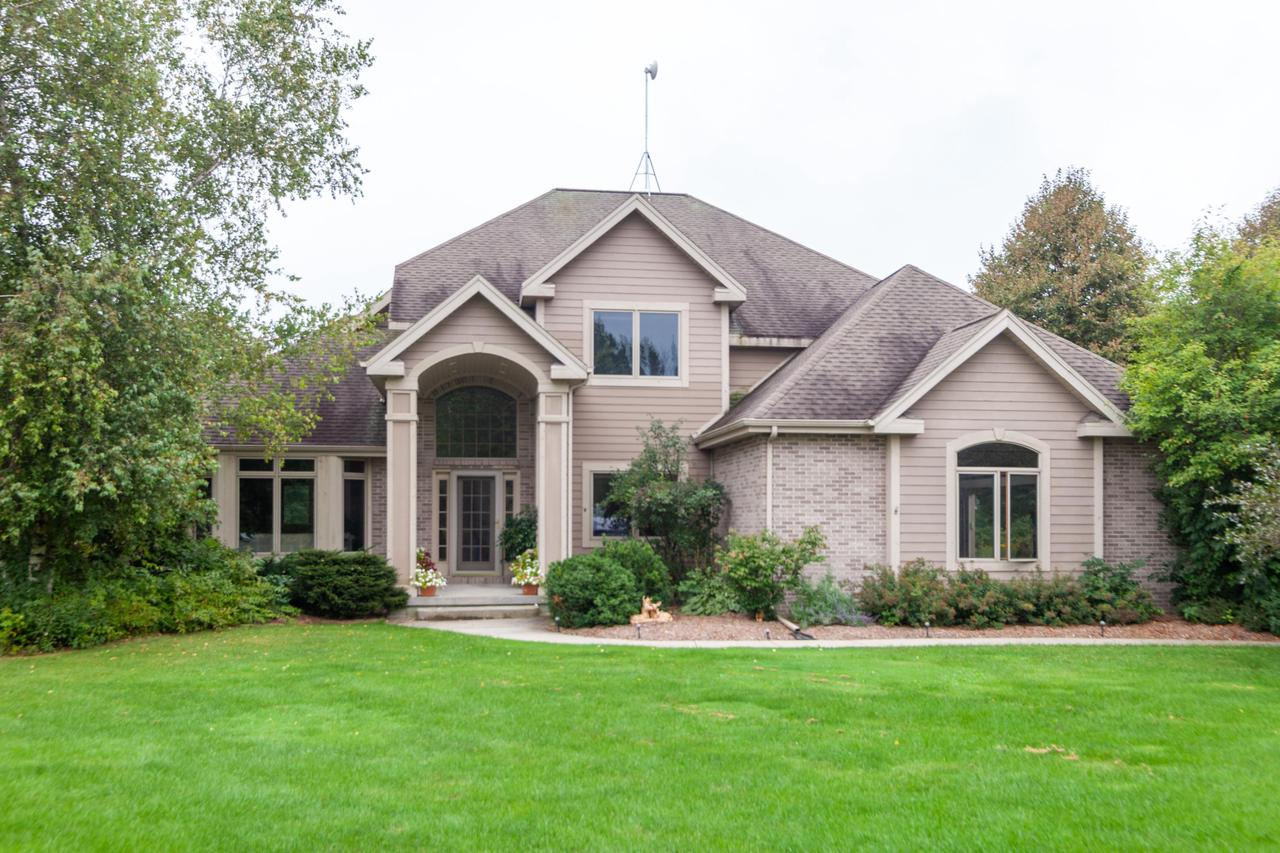 Tucked away on a quiet, country cul de sac you'll discover this stately 4 BR, 3.5 BA colonial on 2.6 lush acres. Kit w/refinished maple HWF+ cabinets ,island w/corian counter+,5 burner stove top,  wet bar, sunny breakfast nook+2nd staircase to upper level . Fam rm w/gas FP, entertainment center+B-I bookcases. Combo office+ laundry rm+ 4 lockers in mud room. Huge master BR w/2 W-I closets and bath w/whirlpool+shower and dbl sink vanity. LL has 12 course basement with sauna and full BA--plenty of room for future fam rm. 3.5 car garage has steps to lower level. Other features: 6 panel doors, lots of ceramic tile thruout, central vac, B-I  speakers,and air to air exchanger. Minutes from Hwy 41+45. Sought after Slinger schools. If peace and tranquility is what you yearn for; this is it!