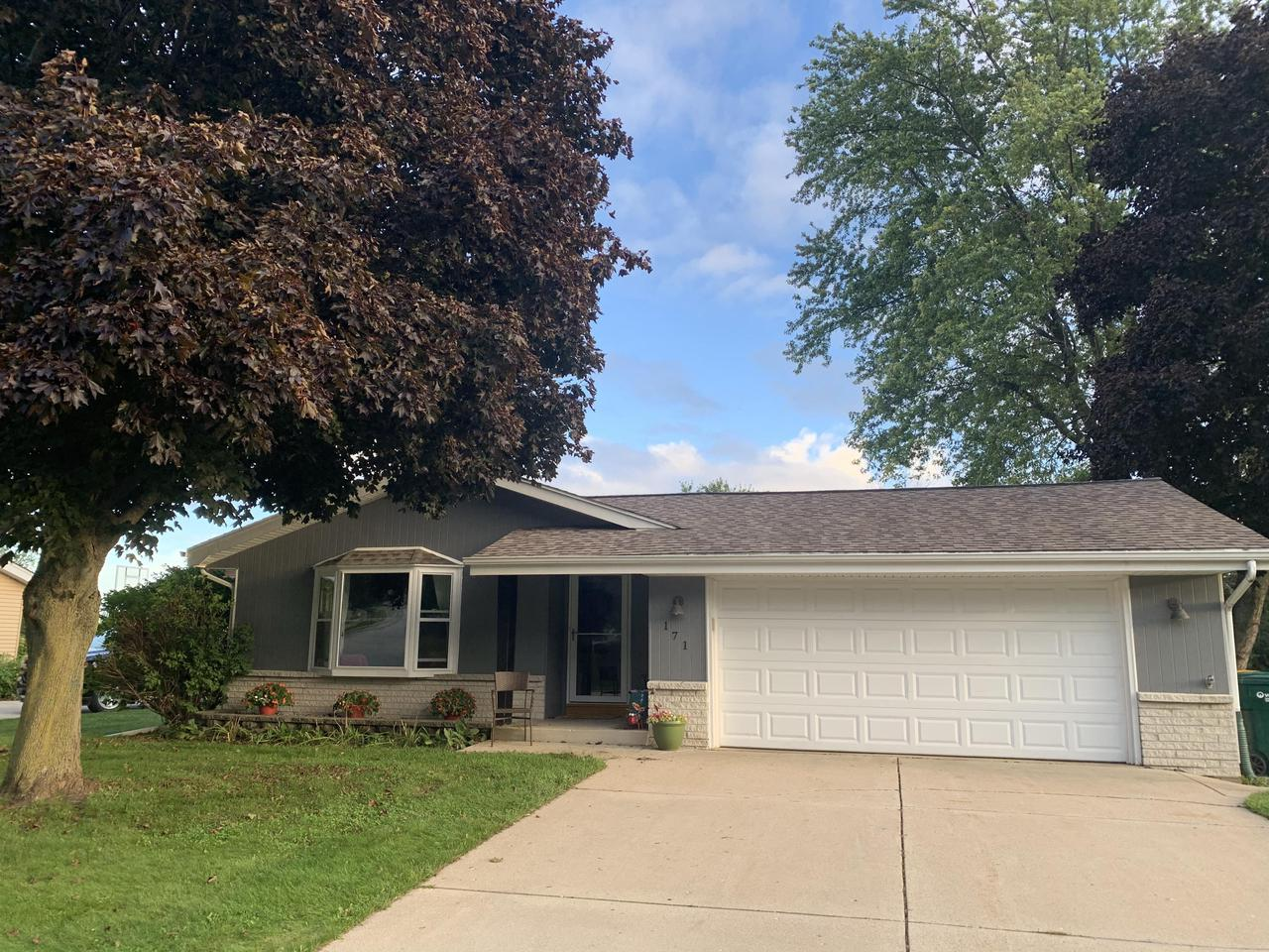 Don't Miss This Updated 3 bedroom, 1 full and 2 half bath ranch with natural fireplace near shopping and schools. Large eat-in kitchen plus dining room open to living room. Roomy village lot with mature trees that abuts the bike path. All updated bathrooms, kitchen with stainless steel appliances and hardware, new siding, new exterior doors, new bay window with window seat, new central air and water heater, great storage. Hardwood floors throughout living room, dining room & bedrooms.  It also features a custom basement with faux-fireplace for additional living space.