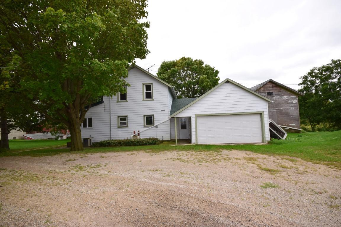 Come see this 4 BR, 1.5 BA hobby farm on 7 acres with numerous outbuildings.  Property is set well off the road and is surrounded by corn fields making it very private. House features large eat in kitchen with snack bar and pantry.  Entertain in the Family Rm, built in desk and storage closets. Main floor Bedroom and laundry. The Master with half bath and 2 other bedrooms upstairs. 2 Car attached garage. Outside you will find Original log homestead Pole building, Steel roof Barn and other outbuildings on 7 acres. Additional acreage available. Bring the animals, use as storage rental, the possibilities are endless. Call today!