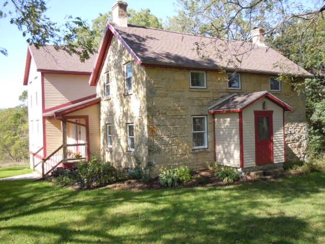 This beautiful country property has the best of the old and new.  The original stone house has been meticulously restored and the 12 year old addition features the highest quality materials in the wood and tile floors, bathrooms, windows and fixtures.  This private location overlooks a valley across to a wooded hillside from the covered porch and living room.  There is also radiant floor heating for maximum comfort. Has a nice variety of tillable and wooded land, ideal for farming and hunting.  Near Military Ridge Trail and Blue Mounds State Park.  Also includes parcel 106-0209.03B and 106-0209.03
