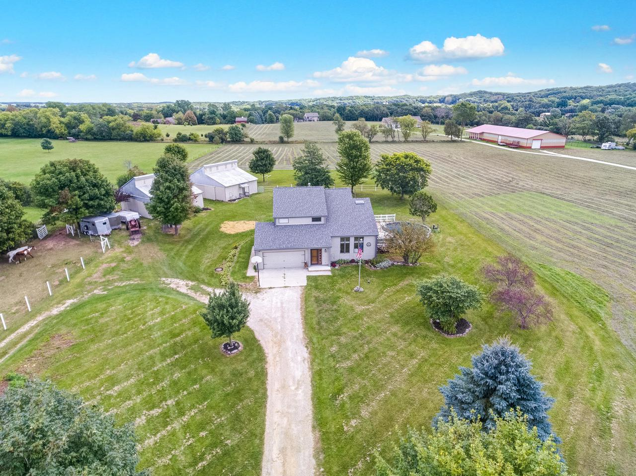 Welcome to this Picturesque and idyllic Hobby Farm in the Heart of the Kettle Moriane. 5 Acres awaits you  w/ cthdrl ceilings, Gorgeous kitchen that truly shines w/ Granite, huge island & space for table that seats 8 plus!  Sunroom off the kitchen w/ a wall of decorative lead glass  doors into DR, kitchen,& LR overlooking the pool& hot tub. Grey wood tiled floors&white woodwork, &skylights brighten it all& main flr laundry& another patio are bonus! Upstairs boasts 3 lrg bdrms&master suite w/ oversized walkin tile shower w/ exposed shower panel of  jets& 2 sinks. Step outside to the equestrian site of this home& 4 stable barn w/ hay loft & tack room. Fenced pastures & riding space! Other building on the property for the hobbyist or contractor.All this close to Ice Age&Glacial Drumlin Trails