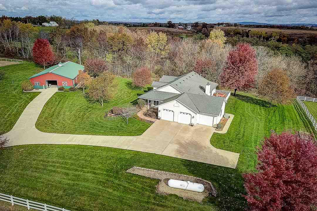 Exquisite & expansive Ranch nestled on 35 acres is ready for horses or cattle! Heated 62x36 metal outbuilding w/4 stalls, tack rm, office & 1/2 bath. Fenced-in sand outdoor area & 2 paddocks w/vinyl fencing. Mowed trails through the 19 acres of woods for 4-wheeling & hunting! Quality features in home incl: great rm w/maple flrs, tray clgs, wood burning f/p & walk-out to new deck. Huge eat-in kitchen w/quartz counters, island & hickory cabinetry. 3 bdrms & 2 baths. Stunning Master Suite w/2-sided gas f/p, tub, walk-in shower & 2 walk-in closets. ML laundry & 4 car attached garage. Just 10 mins from Mt Horeb or New Glarus! VRP $549,900-$574,900