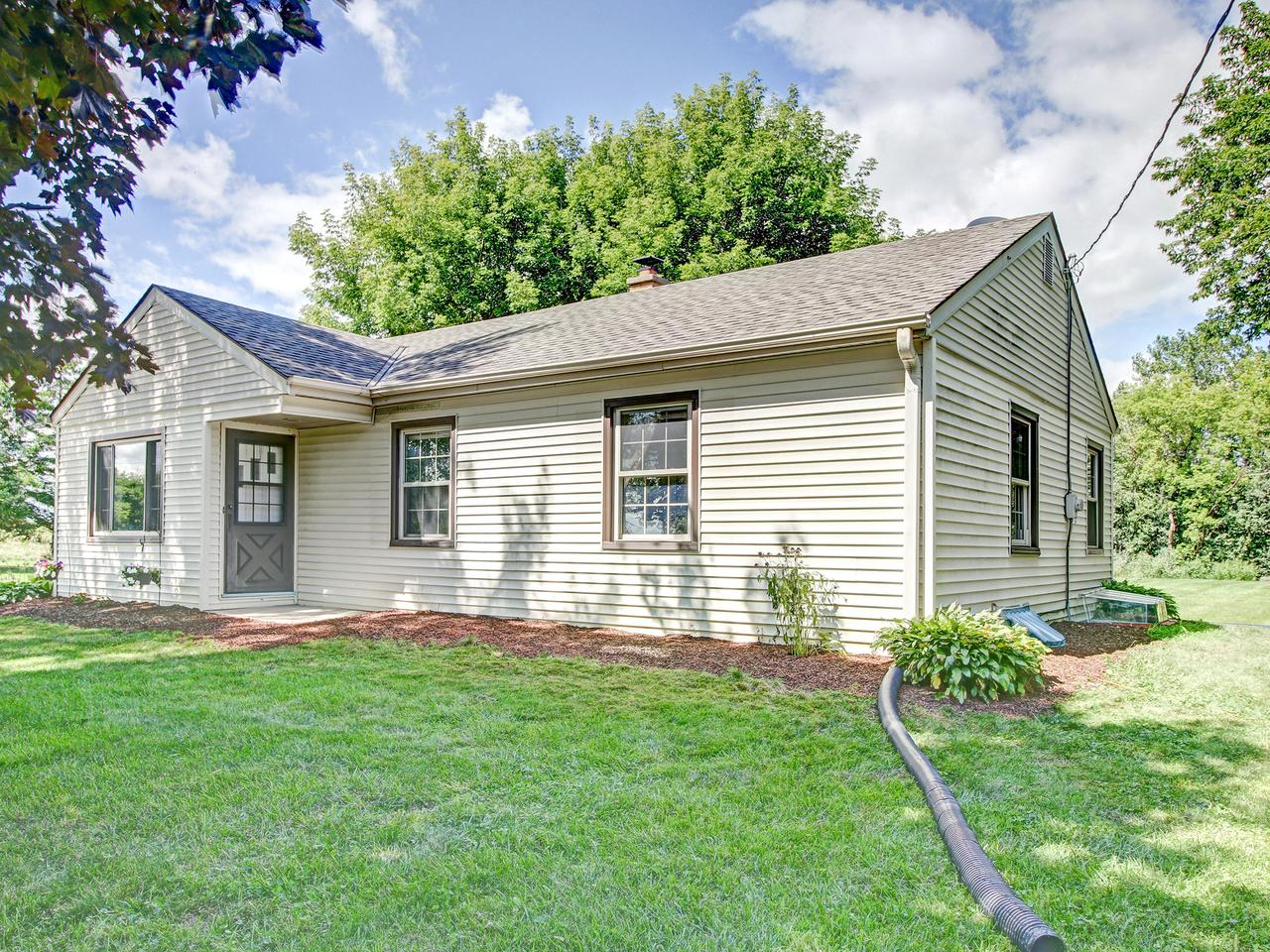 Super adorable ranch situated on over one acre across from 438-acre Mequon nature preserve/park with trails. Brand new (to-be-built) 2 car attached garage w/mud room.  Refinished hardwood floors flow throughout.  Eat in kitchen with breakfast bar, newer cabinetry, recessed lighting, updated countertops, and stainless steel appliances.   White trim and doors. newer windows throughout. Updated bathroom with tiled shower and jetted soaking tub. Bedroom 3 includes wardrobe closet. Lower level has been insulated and dry-walled for added living space. Egress window, plumbed for second full bath (currently office), and epoxy floor.   Electrical and plumbing has been updated.  Shed, extra parking space, fruit trees -pear, apple and peach, mature trees, plenty of room to roam. Chickens allowed.