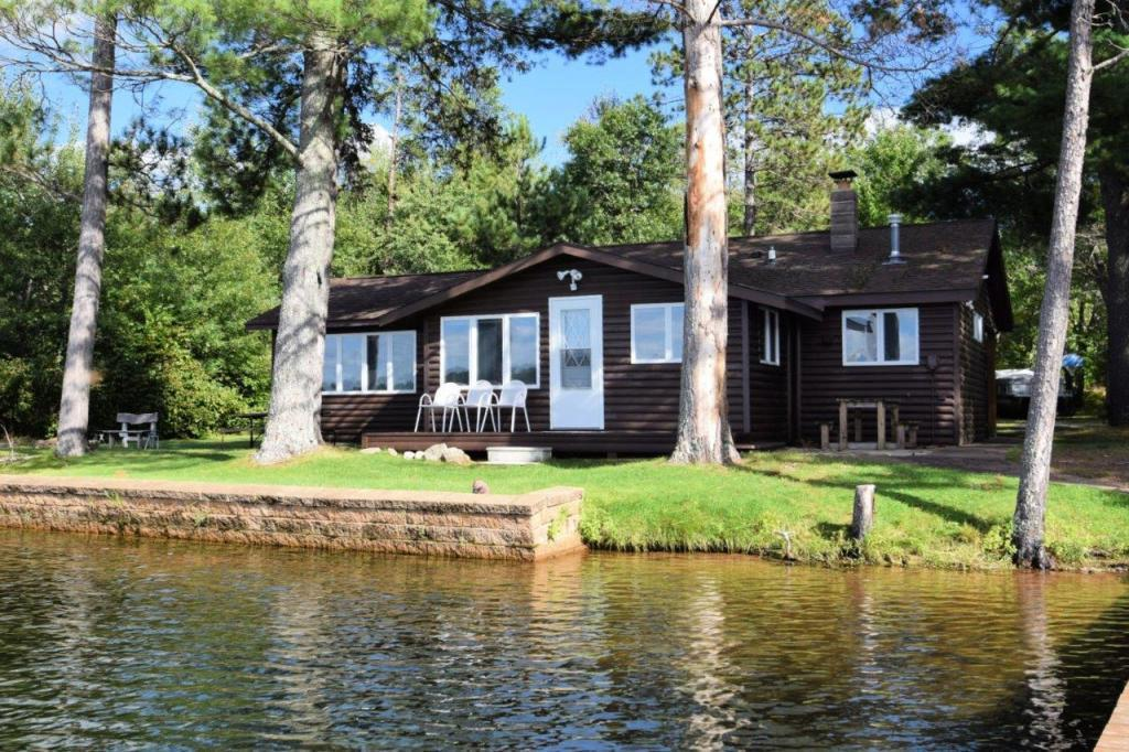 Charming nostalgic log sided 2 BR, 1 BA cabin has it all, including being sold completely turn-key w/rowboat!  444+ ft. of gorgeous level sand shoreline w/2 docks perfect sand bottom, 4.14 acres, tall majestic pines and on highly sought after 194-acre, 21' deep crystal-clear Horseshoe Lake near the Minong Flowage!  Absolutely perfect swimming and offers great fishing and boating. 2 car det. gar. w/lean-to and finished bunk space above, new septic 2019. Interior of cabin is finished in all knotty pine w/laminate floor, nice sized kitchen w/island, dining nook & large living area. Incredible westerly views from the kitchen and just a stone's throw from the water's edge!  Blacktop drive, gorgeous park like setting, sauna house, privy and ATV & snowmobile trails galore! This is your perfect lake cottage!