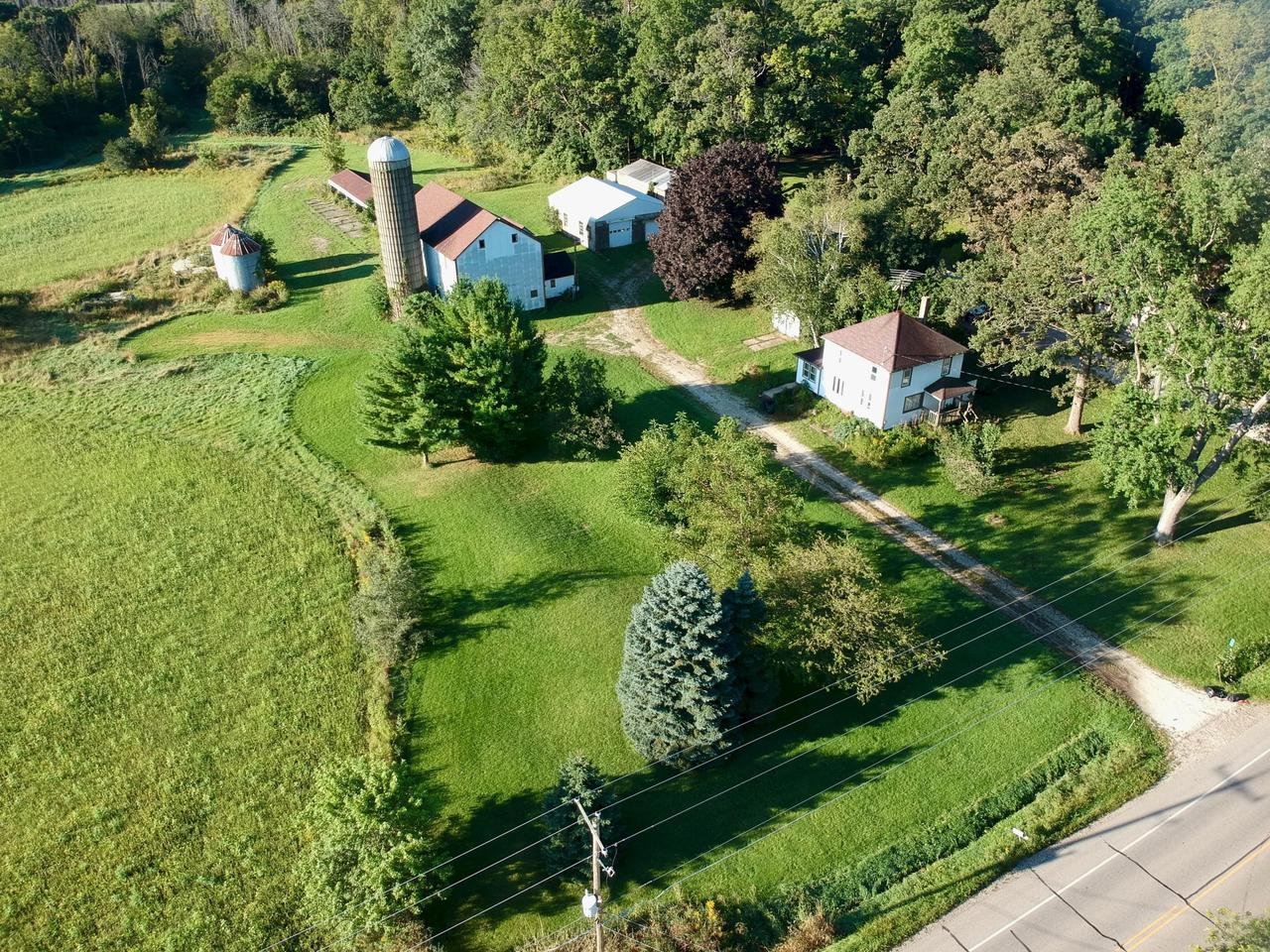 Classic American farmhouse w 3 bdrms, 1 full bath, large living room, dining room, kitchen and sunroom on 5 acres. Dwelling has gas forced air heat, central air, 220V elect & a detached 2 car garage.The property has a 52'x31' barn, & a 40' x 36' garage/workshop w/water & 220V, great for a builder or hobbyist, w 2 doors, 9.5' and 7.5' tall & new roof & trusses in 2012. There are several other outbuildings including a 125' x 18' storage shed and another 20' x 10' building that was used as a granary.  Horses and other livestock are allowed (2 cows or horses, six sheep or goats).  Property would also lend itself to boarding dogs.  It is bounded on 2 sides by Bristol Woods County Park that has over 4.5 miles of trails.  Post & beam barn is a perfect candidate for a barn to residence conversion!