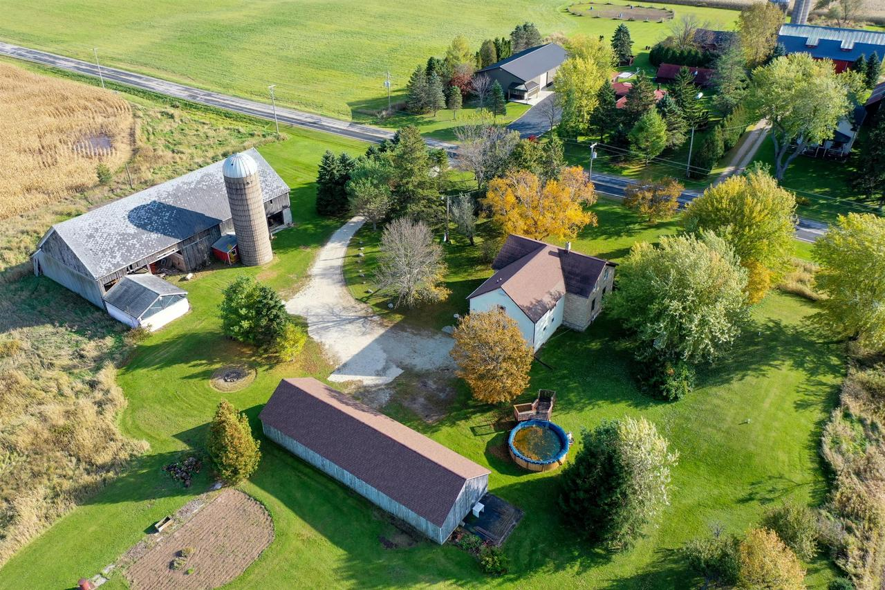 This well maintained farmhouse is located on a 5 acre parcel complete with a small fruit orchard, an outdoor pool, a 6 car detached garage, an insulated & powered ''Milk House'', and a barn in need of some TLC.  Once used as a multi-generational home. Complete with 2 full kitchens, 2 living spaces, and 4+ bedrooms, it could easily be converted into a a 2 family home. Country living at its finest, while still being a short bike ride away from Howards Grove's Schools.