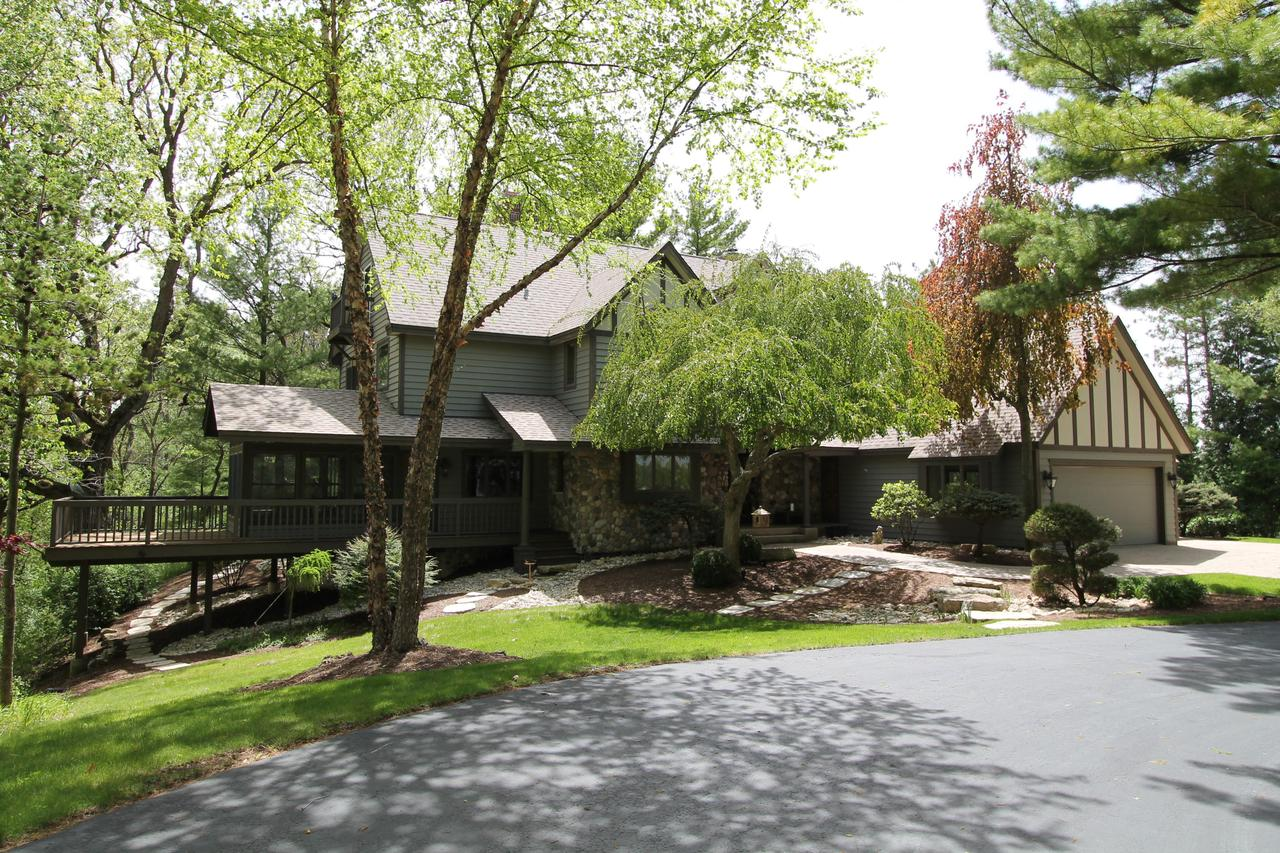 Extraordinary Estate on +/- 7 acres! If you love the woods and water this is a must see! The attention to detail is magnificent in this custom built Tudor Large living spaces, with 2 sided fireplace to an entertainers kitchen. The 3 season room features a wood vaulted ceiling and a deck with a mile long view of some of the best nature you will find. The library is completely custom with hand built oak paneling. Expansive views from the master suite will start your day off smiling. Fully finished walk out lower level, 3 car garage and professionally landscaped grounds complete this amazing property. Property is subject to land division.  More acreage is available.