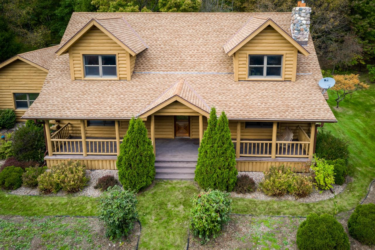 Beautiful log home nestled on over 4 acres offers first floor MBR & laundry, first floor to second floor vaulted ceiling in living area, floor to ceiling stone fireplace, 4 season sunroom just perfect for viewing nature from birds to deer! Enjoy the private back deck or  8' x 47' front porch! There is a large 2-story outbuilding perfect for a workshop or storage. Plenty of perennials throughout the year and a beautiful magnolia tree that blooms every Spring! If you are looking for a private, rustic, well maintained home...this is it! Plus, new gutters to be installed by end of October around whole house. New shingles on outbuilding to be completed by end of October.