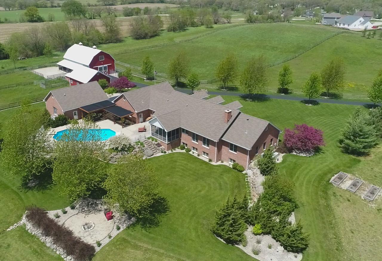 Impressive equestrian estate on over 35 rolling acres in Town of Waterford. This brick custom built ranch offers over 4300 square feet of living space, with heated attached 4.5 car garage & detached 3.5 car garage. Enter the amazing open concept kitchen & great room w/beamed vaulted ceilings overlooking 40x20 inground solar heated pool. A spacious master en-suite offers split floor plan with 2 other large bedrooms & Jack N Jill bath. Downstairs is a recreation room, another bedroom, craft & exercise room & full bath. Walk up to garage from the lower level for convenience. Loads of storage with a main barn offering 2300 Sq. Ft. with a loft, tack room & 3 stalls. The newer 3200 Sq. Ft. heated pole building will hold your RV w/electric hookups and attached heated workshop.