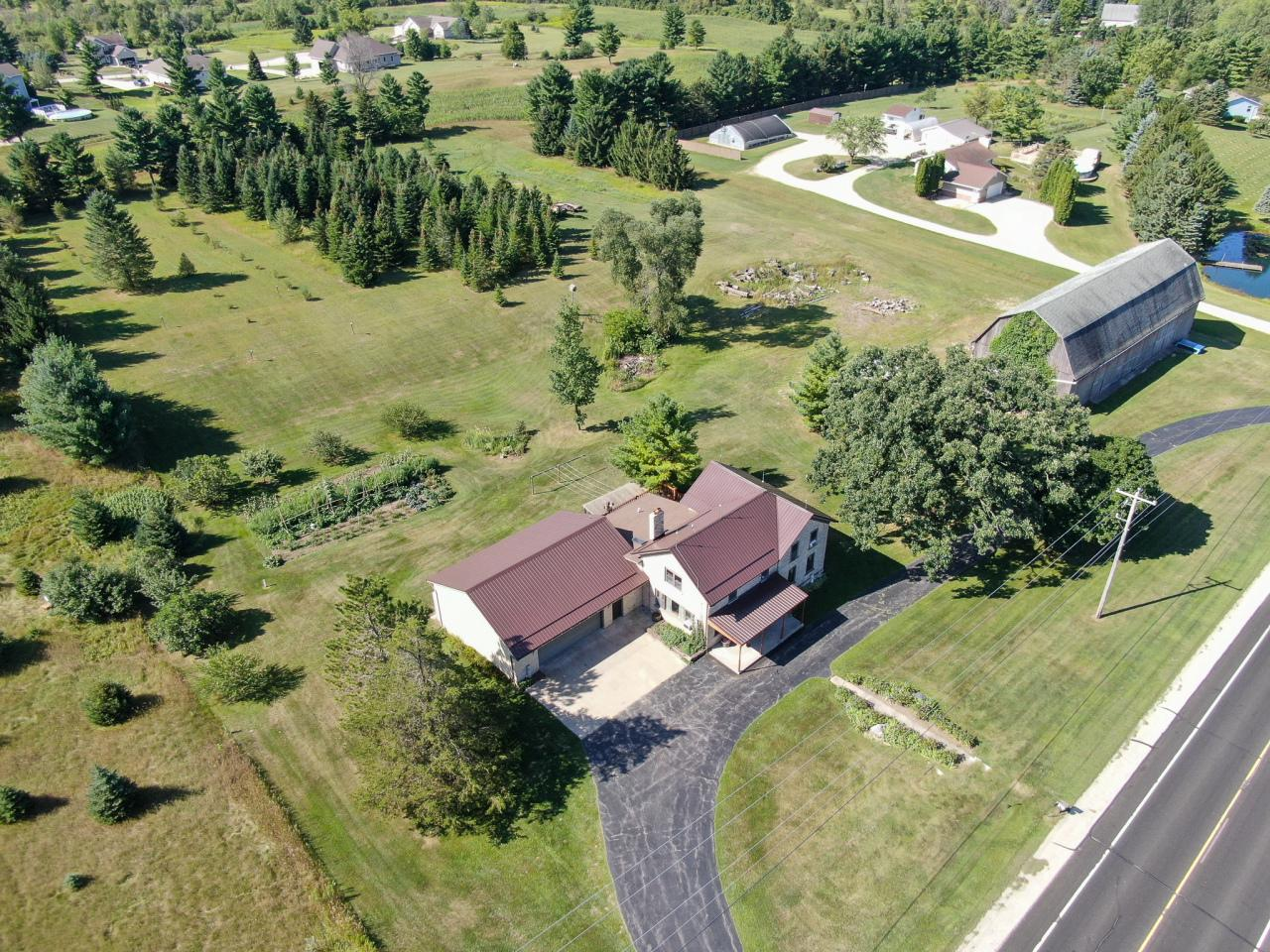 Beautiful, spacious, restored cream city brick farm house on 4.55 acres w/a 2 story barn is a must see!  Barn (120 x 40') used for seasonal storage  brings in approx. $3,000 for winter storage.  Owners have hosted a wedding on barn's upper level.  Custom built cabinets, solid oak doors, wood trim spindles, staircases & two-tone HWF's. Walk the land to appreciate the mature trees, perennial flower gardens, fruit trees, organic vegetable gardens & PRIVACY!  Updated triple pane Weather Shield windows, thick insulation, new shingle & steel roof in 2017. 3 zone hydronic heat furnaces for wood/gas.  Attached 2.75 car GA w/LL walk out basement shop. Main level MBR w/room to add MBA.  Large open KIT, LR, dining areas w/a full BA and 25 x 5 ft. main level laundry/mud room.  Horses allowed.