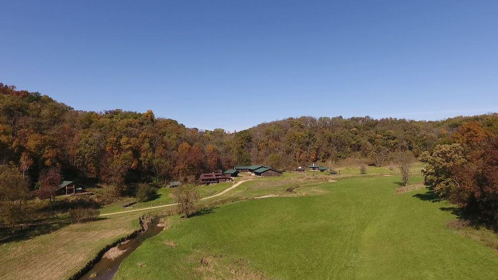 In the Mississippi bluffs of Wisconsin?s Driftless Region, at the end of a private road, is this incredible 94.4 acre property that is close to town. The stream flowing thru serves as a wildlife magnet. Includes 2 homes (log and timber frame) with many recent major improvements including kitchen, bath, and roofs. Outbuildings include a large insulated/heated shop and some suited for horses and livestock. The land is a mix of woodlands and pasture. Possibilities include a residence, retreat, bed and breakfast, livestock, small business, and dude ranch. Listed sq. footage includes both homes.