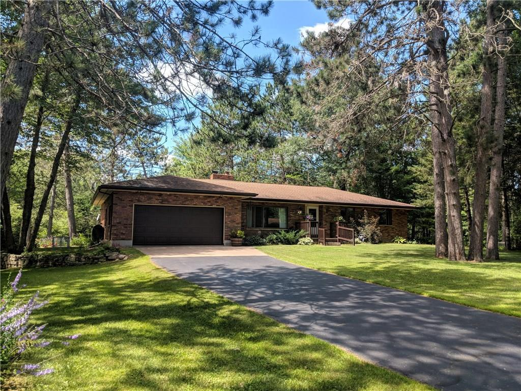 This beautiful 3-bedroom home has a park-like setting surrounded by mature hardwoods in the middle of 14.68 acres!  Private location, between Bruce and Ladysmith.   The exterior is attractive red & brown earth tone Brick with Anderson windows and limestone window sills.  The interior is includes a fully equipped Kitchen, first floor laundry, 1 1/2 baths, 3-bedrooms, office, 3-season room, and living room with a 3-sided brick and walnut fireplace.  2-Car Attached Garage plus extra 2-Car Garage.