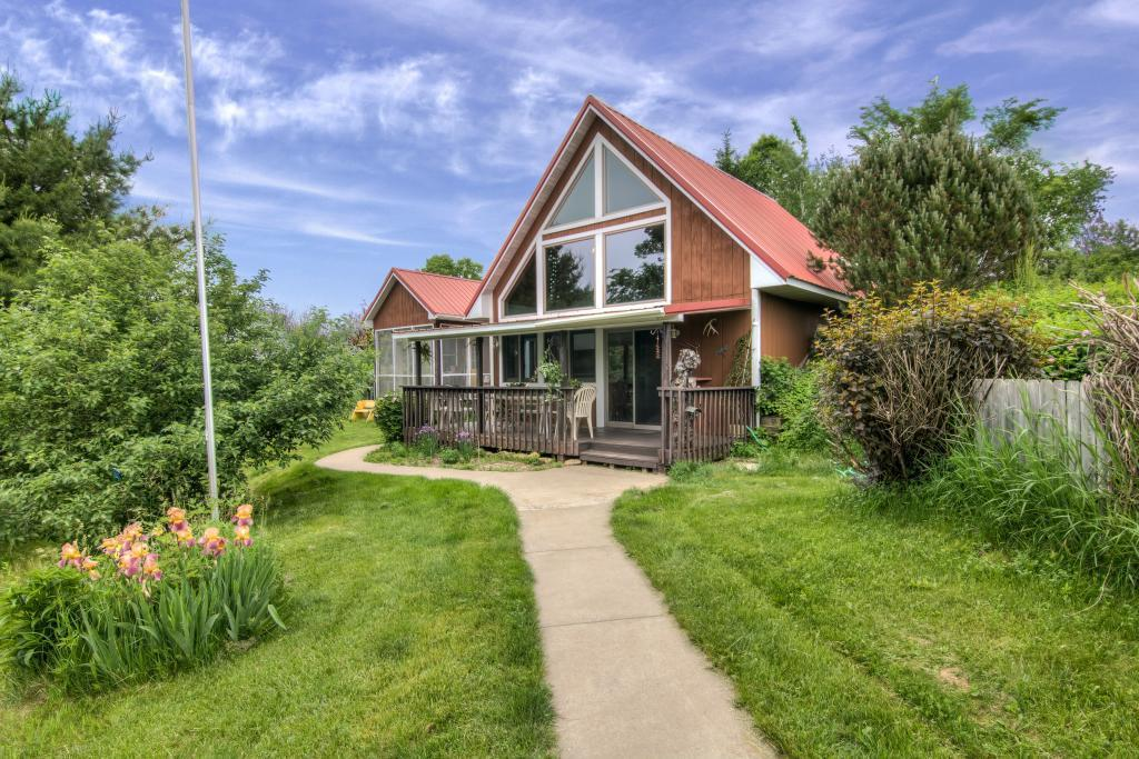 Built in 2001, this 2 BR, 1 BA home has an attached cabin that was built in 1998. The entire main living space has been freshly painted. The house is built on a slab.  It has an unattached 2 car garage with an insulated small room 14x12 above.  The main source of heat for the house is in-floor hot water heat (electric water heater).  There is also a gas fireplace in the house, a small wood burning stove in the cabin and a pellet stove (Quadrafire) in the room above the garage.  A load of wood pellets comes with the garage. We are located 7.9 miles from the Ellsworth Fired Hall.  The house has its own well and septic system, LP gas  (River Country Coop) and a small Skystream wind generator to help offset the electric bill.  There is a 20 X 12 garden storage shed (no electric) with cord wood walls and a sedum roof close to the house. The property consists of 30.45 acres of hilly, wooded and open land with mowed walking paths in Section 6 Salem twp. 6 acres of farmland rented $612/yr