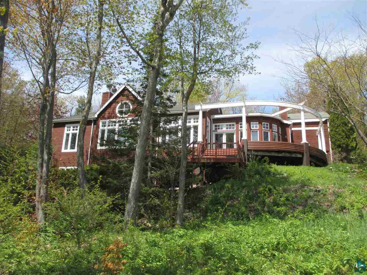 This exquisite home has spectacular views of Lake Superior and almost the entire length of Madeline Island from just about every room!  Right outside Bayfield on a large wooded and very private 2-acre parcel, you'll see the daily changing nature of the Lake, with fantastic sunrises and night skies. This top quality home has a thoughtful floor plan, designed to maximize Lake & Island views, providing open spaces for gracious entertaining and private areas for relaxation, study or work. High ceilings, hardwood, tile and slate floors, floor-to-ceiling windows, gently curving walls and multiple fireplaces to warm your heart!  Main floor has a large master bedroom/bathroom suite and lower level adds two more bedrooms, family/rec room, kitchenette and plenty of storage space. Huge wraparound deck & lower patio. Perched above the fairways at Apostle Highlands Golf Course, with that sweet southeasterly Island view, you'll find beauty, quiet and solitude any season of the year! 2 Extra lots available for $20,000 combined.