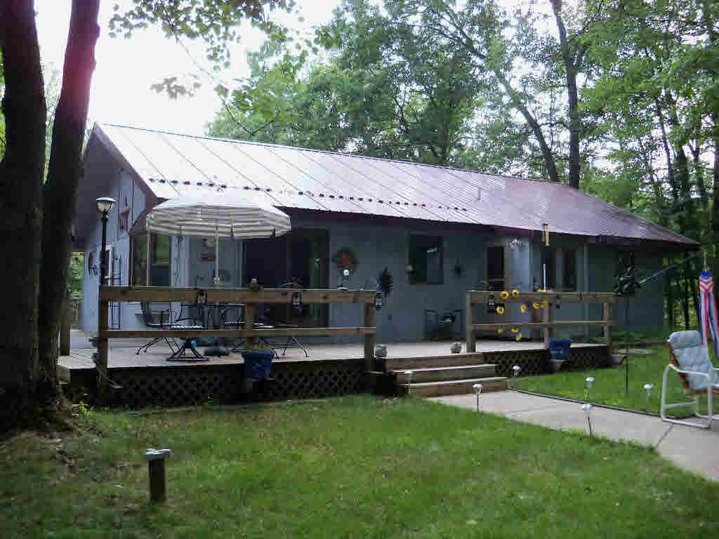 Looking for a get away? Look no further! Home w/privacy, nestled in the trees. Have a green thumb? 3 heating options wood, baseboard, and electric forced air and the comfort of central air.  Basement w/green house ready to go. Location-vacation hot spot. Tons to do: like to fish, hunt, raft, rock climb, hike, horseback, ATVs & MUCH MORE!! Space to entertain inside & out. Gather around the fire pit & enjoy. This price includes the cabin and the lot that it is on.  Three additional lots are available.