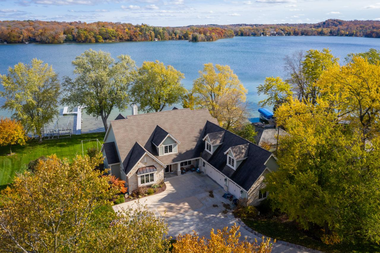 This amazing waterfront property has 147 ft of level frontage on Big Cedar Lake. A winding driveway leads to a courtyard & main residence, a French Country style home w/ 4925 sq ft. Brazilian HWF on most of the main level. Gourmet KIT w/ custom cabinetry, large island w/ seating & cooktop, an addtl island & pantry. Enjoy the morning room or step out onto the entertainment sized deck. Formal dining room is comfortable, yet luxurious. Great-room w/ soaring ceilings, stone FP, stairway to upper level, & wall of windows w/ lake views. Main floor MBR w/ lavish BA has jet tub, steam shower, vanity w/ an in mirror TV. Walk-out LL with family room includes fireplace, KIT, exercise room, BR, full BA & more. Sun room w/ incredible views. Attached heated 3.5 car roadside GA & 900 sq ft lakeside GA.
