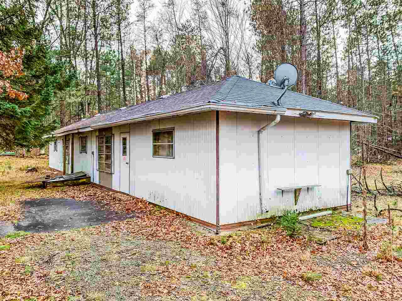 """Enjoy your slice of the Northwoods! Serene 1.81 acre wooded parcel adjoining the Nicolet National Forest. Property includes a 24'x32' garage. Sand point well and septic. Selling """"AS IS"""". Older mobile home onsite needs removal. Located just minutes from Flower Lake & Crooked Lake . Ideal land to Hunt, Snowmobile & ATV, all from your back door!!"""