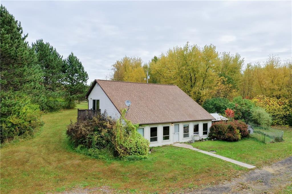 Location, Location!  This 5+ acre property is south of Eau Claire surrounded by woods and fields. Just a little TLC needed to make it really shine!  Open concept throughout main level with woods flooring throughout kitchen/dining/living room and in-wall gas fireplace. Upper level features 2 large bedrooms and full bath. There are 2 rooms on main floor that can be an office, den, gameroom.  Property features lean-to building and barn that is ideal for a couple horses.  Lots of possibilities!
