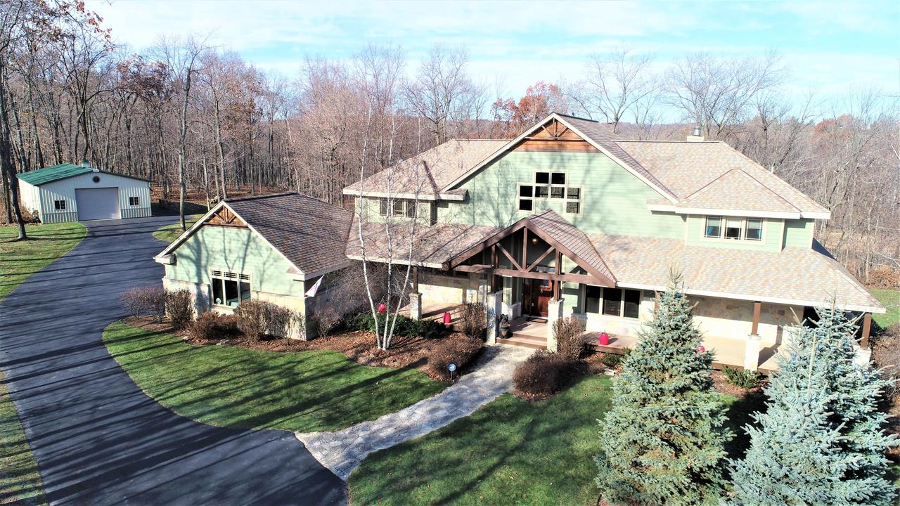 Custom built, executive estate on 11.47 secluded acres of nature/Hunting lovers dream in Slinger School District.  Beautiful chef's kitchen w maple cabinets, hard surface counters, island, and hickory floors. Impressive Great room features GFP and a Grand wall of windows allowing spectacular outdoor views of inground saltwater pool, woodside & creek.  Huge first floor master w sitting area,his/hers walk in closets, and en suite w heated floors/walls w double sinks, soaking tub and walk in shower. LL walkout including heated floors, wet bar, duel sided FP, game room, full bath, and bedroom. Property has frontage on Cedar Creek to enjoy fishing and ATV trails. Huge 50x30 detached garage w electric and water. Perfect for small business owner. Call today!
