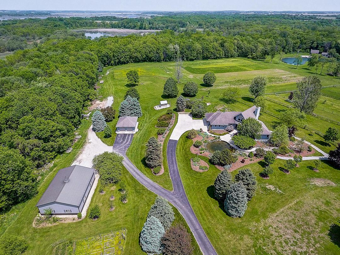 Absolutely stunning 100+ acre estate offers ultimate privacy! Bordered by almost 4500 acres of Mud Lake Wildlife Area provides for phenomenal hunting and wildlife viewing opportunities. Beautiful quality built home offers high end finishes, custom millwork and a wall of windows which overlooks a 1 acre pond with historic 1870s log cabin with modern day conveniences. Enjoy your summers swimming, zip lining, fishing or just relaxing in the waterfront screen porch. Property is currently set up as an equestrian estate with 8 box stalls, heated lounge, 60' X 120' indoor riding arena, round pen, automatic waters, pastures and several run-in shelters. Additional machine shed, heated & unheated shops, green house, apple orchard, vineyard, tillable land offer the option for a variety of uses.