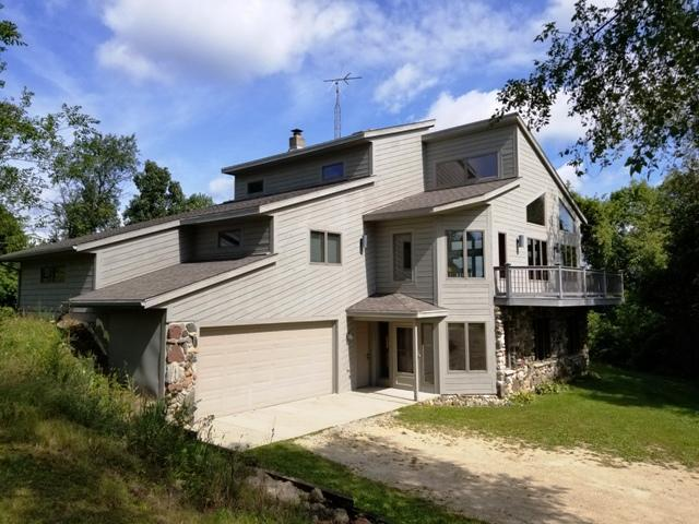 This contemporary open concept design on 7+ ac. surrounded by the Kettle Moraine & DNR lands has it all. C-2 Zoned, woods, meadow/field, park like get-a-way, spectacular views of Bluff Creek nature area, a few steps away from Trout Stream, Ice Age Trail, ski and snowmobile trails, & Whitewater Lake. Fantastic vaulted great room has tons of windows with views in all directions. Beautiful unique oak walls, stair case, floor, & trim were all harvested & milled from trees on property. Huge wrap-a-round deck. 3 bedrooms, 3 baths (one partial finished), plus partially finished bonus room & rec. area with full windows are a plus.  Original owner and first time offered on market.  This is a one of a kind opportunity and should not be missed. Call Today.