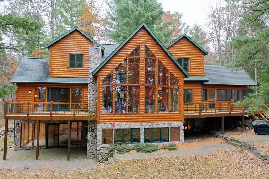 Stunning log-sided chalet on pine covered W facing lot. Great room features floor-to-ceiling glass, fieldstone fireplace, wood floors & log accents. The master has private lakeside deck, vaulted ceiling, & jet tub. Spacious loft has 2 BRs, full BA & sitting area overlooking great room. LL family room has gas log stove, rec area with wall of glass looks out to outdoor shower. Enjoy the outdoors from screen porch, deck or fire pit area. Paths lead to lake or iconic swing that floats over lake.