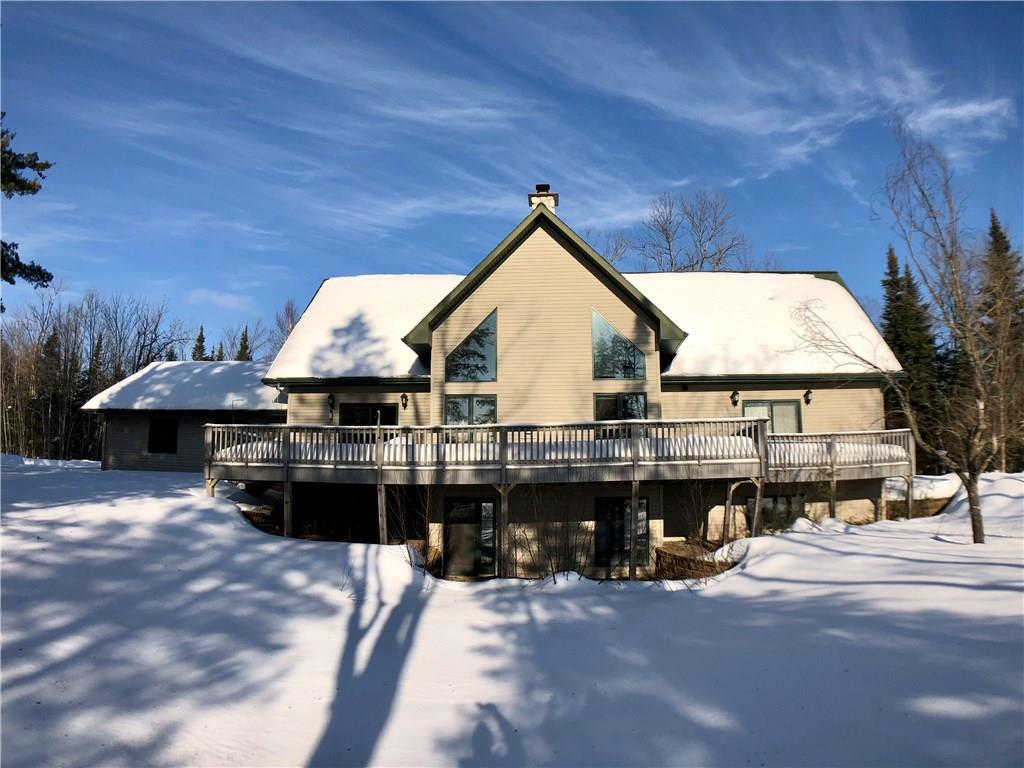 Large 3 BR, 4 BA, chalet on 7.83 acres and 154 feet of level frontage on Trapper Lake.  Vaulted wood ceilings, wood burning fireplace in living room.  Kitchen with walk in pantry, center island, and breakfast counter.  2 master suites, 1 on main level and 1 up.  Jet tub and windowed soak tub.  Attached 2 car and detached 3 car garages.