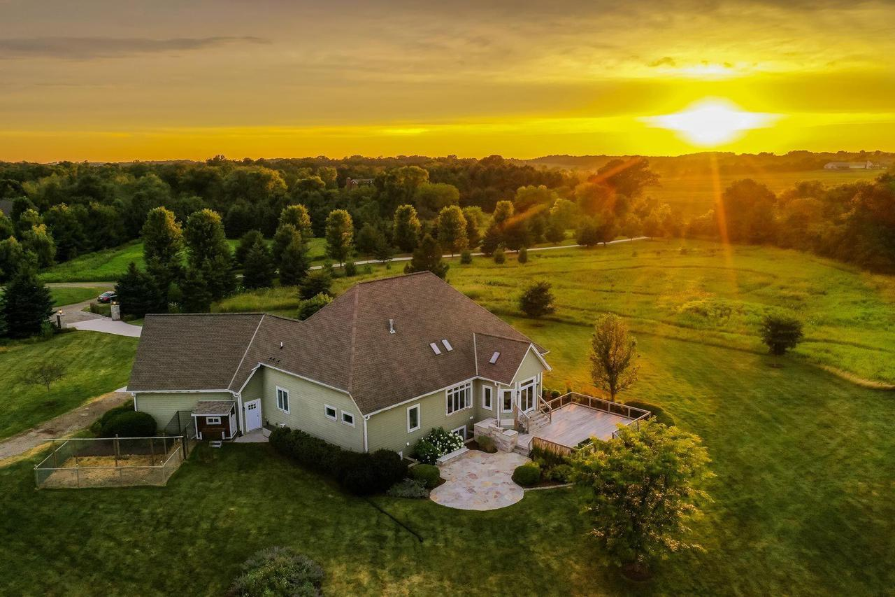 Country living with modern amenities!!! 2 mi south of Erin Hills GC, this 4BR-3 Bath split ranch is sure to impress. Located in a school choice zone & only 1/2 mi from the bus stop. Set on a picturesque 6.5 acre lot, the home provides just under 4400 sq ft of finished space. Custom stone pillars & an exquisite stamped driveway provide a grand entrance. Inside enjoy elevated ceilings, maple HWFs & an abundance of nat light. Kit boasts stone counter-tops, SS appliances & thoughtful touches (wine fridge/pot filler). MBR has tre-ceilings, WIC's & an oversized on-suite. Custom-built wet-bar, hand crafted wine cellar, gym, steam shower & 4th BR make the lower level feel like a separate home. 100 yr Ipe ironwood deck, elec pet containment & over $80,000 of stone work put the cherry on top!!!