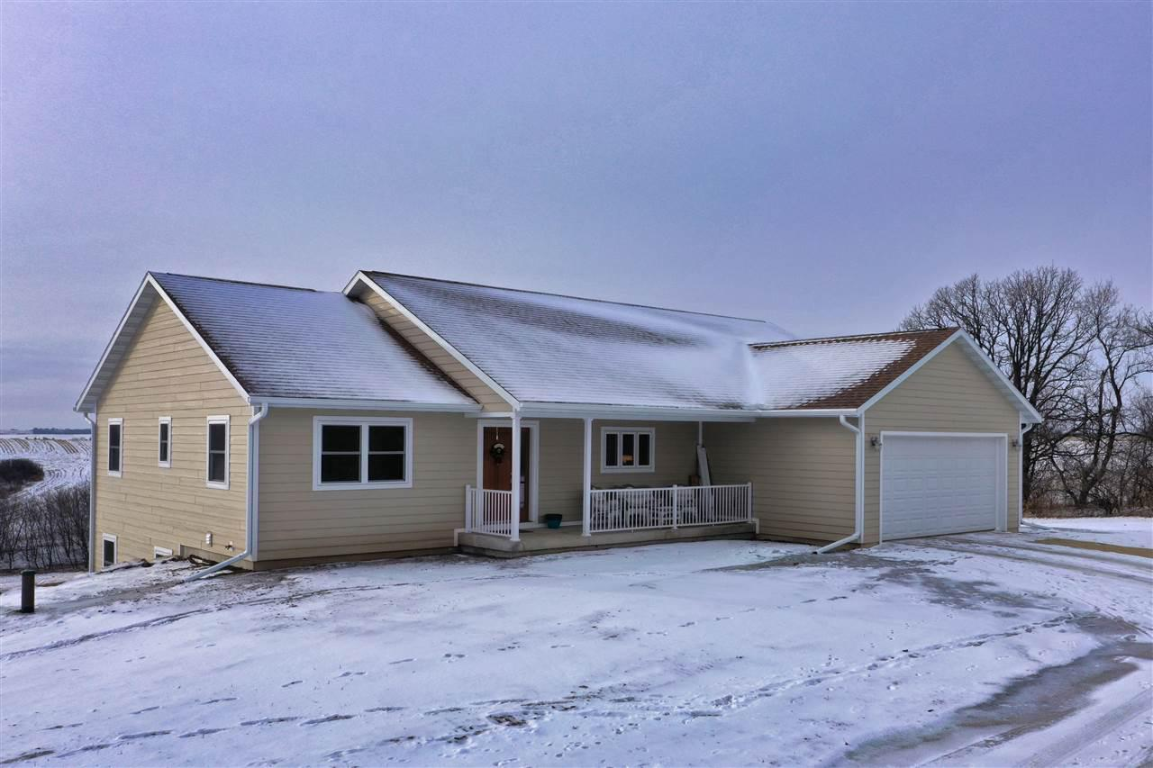 NO SHOWINGS UNTIL OPEN HOUSE JAN 26 AT 11:00 AM. Panoramic views abound from this new custom built ranch home on 5+ acres with southern exposure in the rustic hills near New Glarus . Open flr plan with vaulted ceiling, lg picture wdws with expansive views & cozy gas FP.  All woodwork, trim, doors & cabinets are custom built by skilled Amish craftsman, plus quartz countertops & self-close cabinet drawers in the kit. Spacious walkout LL FR with 4th BR. LL also includes a self-contained mother-in-law suite/efficiency. Attached 2-car garage & separate 28? x 32? storage building featuring another 2 parking/storage stalls with rm for all your toys. Lots of rm on the land for gardening, horses, solar/wind arrays etc. Located on quiet, sleepy tree-lined road with dark skies & countless stars.