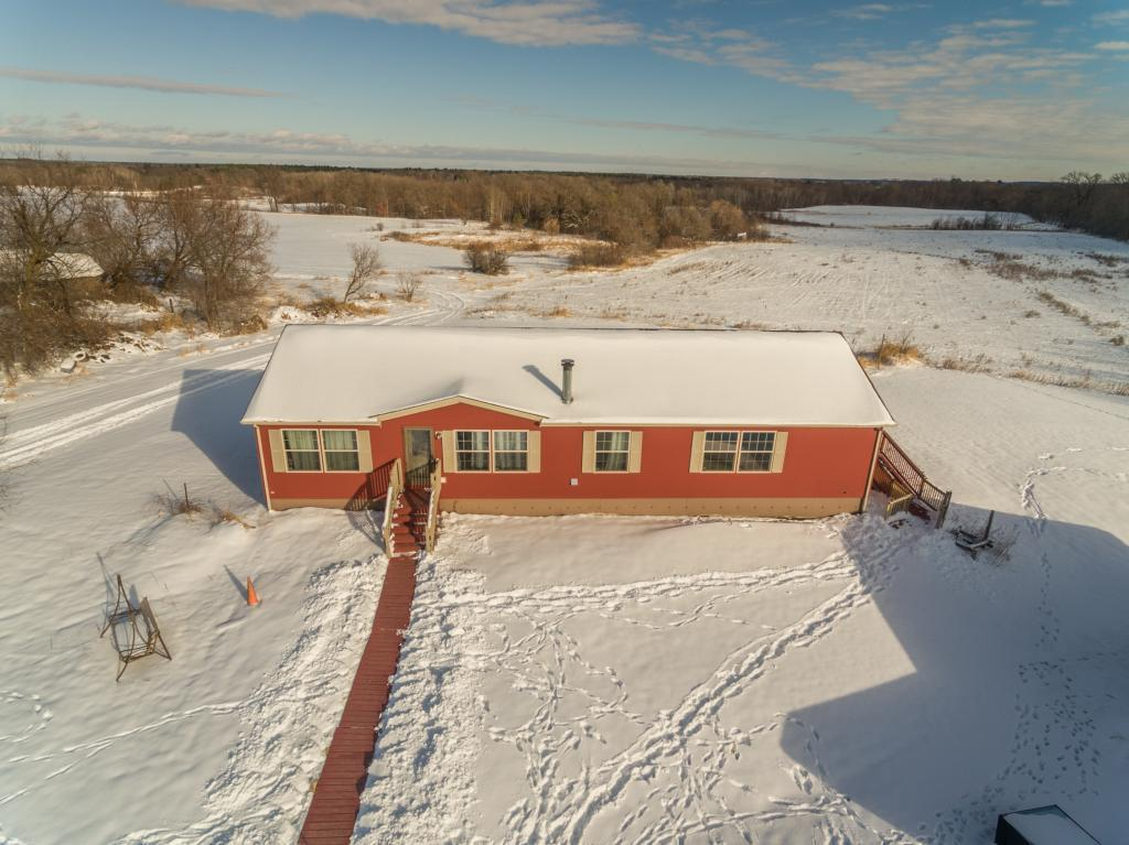 Fantastic home just outside of Grantsburg with over 28 acres that back up to the Wood Lake Camp. With over 2100 square feet of living space and a large deck, this home is the perfect country hideaway and ready for you to enjoy the great outdoors. Also included on this beautiful piece of property is an approx. 42 x 20 foot detached three-stall garage plumbed for in-floor heat as well as a large partially heated pole shed.  There are many upgrades here, including off-peak in-floor heating, two water heaters, and a newer furnace and central air with an air exchanger. Relax in your own private retreat in the large master bedroom with en-suite and walk-in closet and enjoy the views throughout the house through the many magnificent windows with natural lighting. If you're looking to be close to town but still want to enjoy all that Mother Nature has to offer, including plenty of pheasant, deer, turkeys, and other wildlife, look no further!