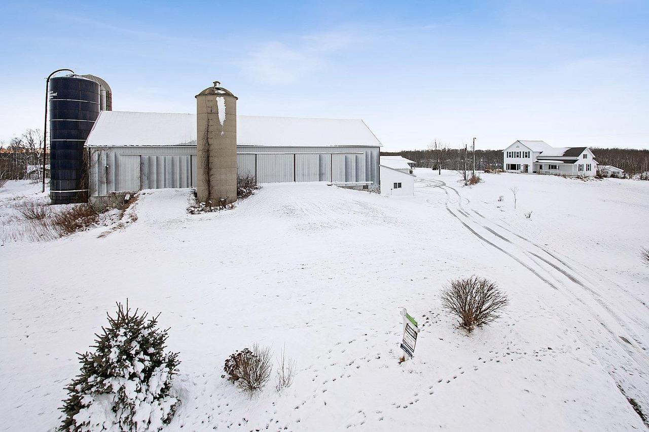 THE VIEWS ARE AWESOME from this hobby farm on the east side of Long Lake. Perched on almost 7 acres you will enjoy endless wildlife and nature at your back door. Farmhouse originally built in 1930 has updates that make it move-in ready. Lg front porch to relax on or decorate, BIG country KT w/center island, living room w/lg pic window. Upstairs is huge EXTRA rm for storage or make it another BR, master suite w/master BA w/dbl sinks, 4 car garage, HEATED workshop bldg 30x48 w/water & more. Barn buildings, machine shed area, mound system, Updated house roof & siding & deck. Check it out