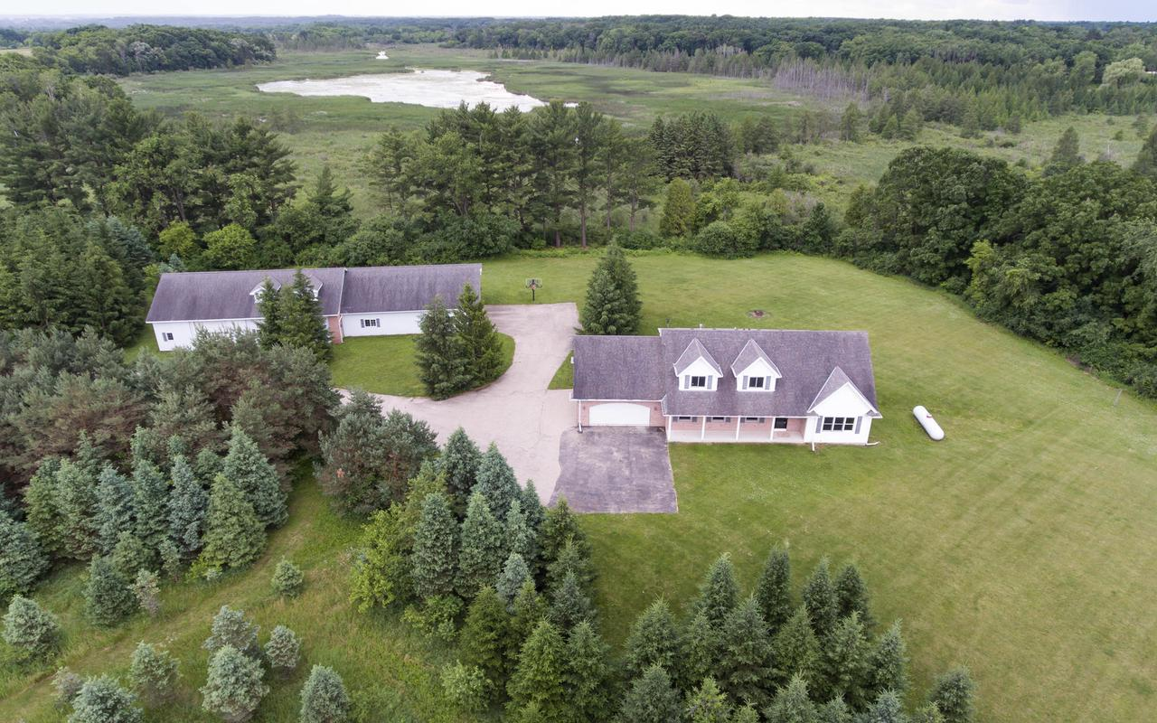 You can admire your horses/animals in their pastures as you enter & drive slowly back to the house on this 35+AC parcel w/partial woods. Private setting offers wildlife & hunting opportunities! Outbuilding offers: 58x38 w/2 box stalls, 21'5x35 heated & A/C workshop & 2.75 GA. Plus an attached 2.5 car GA! New deck, new carpeting, fresh interior paint, new light fixtures, 3 new windows in lower level, all appliances included, plus a 10 kilowatt generac generator! Both pastures have freeze proof water lines that run to heated waterers. Fresh water hydrants installed by entrances to pastures.  3BR home offers 3 full BA, loft area, great room w/fireplace, LG KIT w/granite CTops & BEAUTIFUL views from every window! One Year Home Warranty Included!