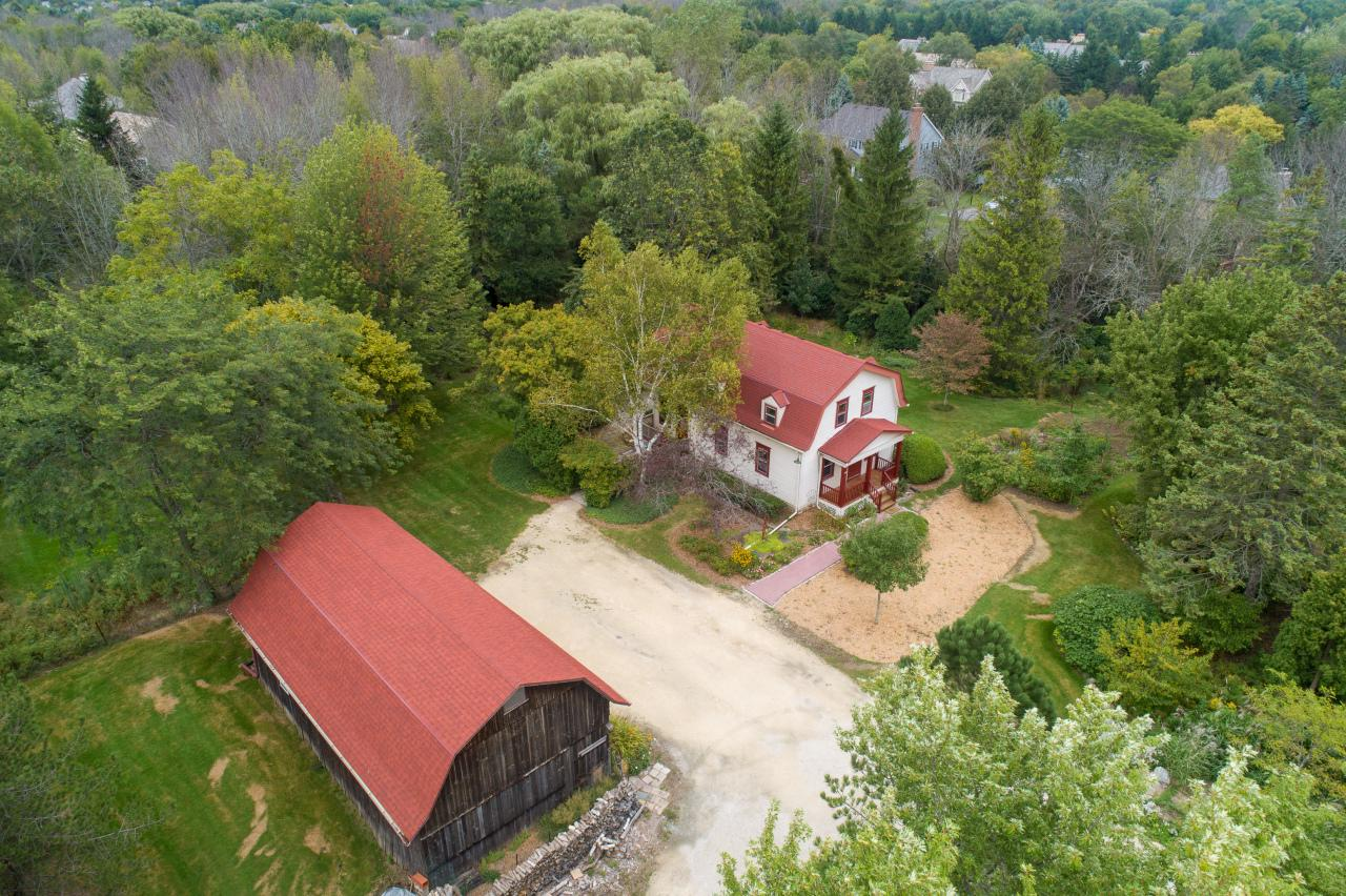 Looking for the charm of a farmhouse with modern updates and a fabulous southeast Mequon location? Need a barn to store the toys? Here's your chance! Act now, it doesn't come up often. Southeast Mequon charmer with an open concept main level with a versatile floorplan, fresh new kitchen yet the details you would expect from a 1900's farmhouse.  Cozy family room with vaulted ceilings and a wood burning stove and three bedrooms including a large master with adjacent bonus room and a full bath on each level. This very private, almost one acre lot is enhanced by a large barn with a loft and space for parking the cars, boat or camper. This is an unbeatable opportunity to make your dream come true.