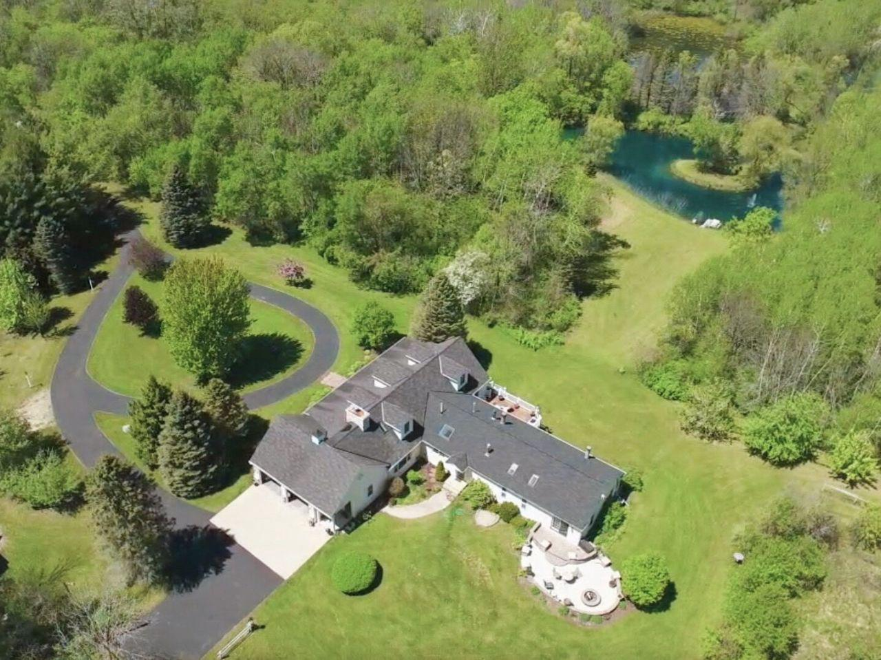 This spectacular property of almost 20 acres is nestled in pristine woods & surrounded by water. This 5,000+ sq ft home is closer than you think...15 min from Cedarburg, 30 min from Kohler's magnificent golfing. Featuring 600+ ft of Milwaukee River frontage, 1/3 acre pond stocked w/ perch & other pan fish. Wildlife is abundant throughout the property around the corner from Waubedonia Park. The home is spectacular w/ over 1,200 sq ft of living space added in 2001. 1st floor master suite, spectacular master BA w/ sauna, multiple fireplaces, walk-out LL w/ guest suite & 2nd KIT, multiple outbuildings including a 4 car heated GA w/ finished living area above. Too many extra amenities to mention, pictures don't do it justice. This is a must see home & property. Close to Road America!
